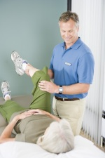 Photo of therapist performing manual therapy on an older woman's leg