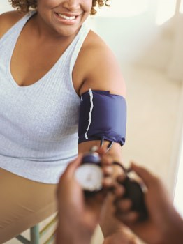 Photo of a woman having her blood pressure checked by a health care provider
