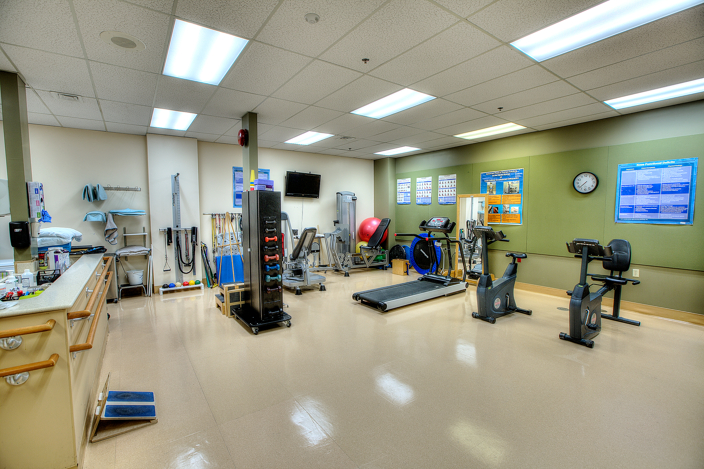 Gym containing physical therapy equipment like treadmills, bikes, and stretch bands