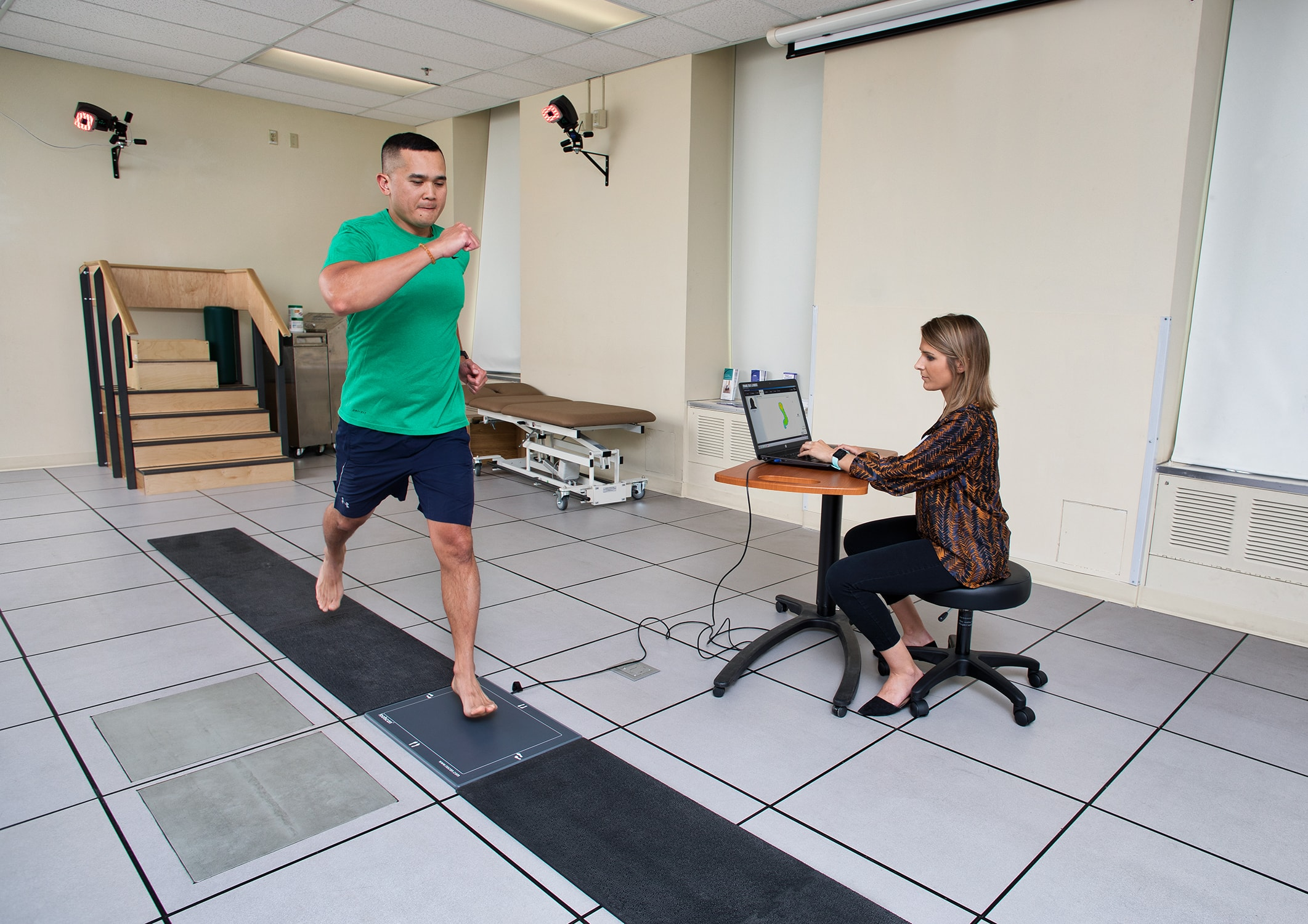 A man running while hooked up to motion sensor gait analysis equipment