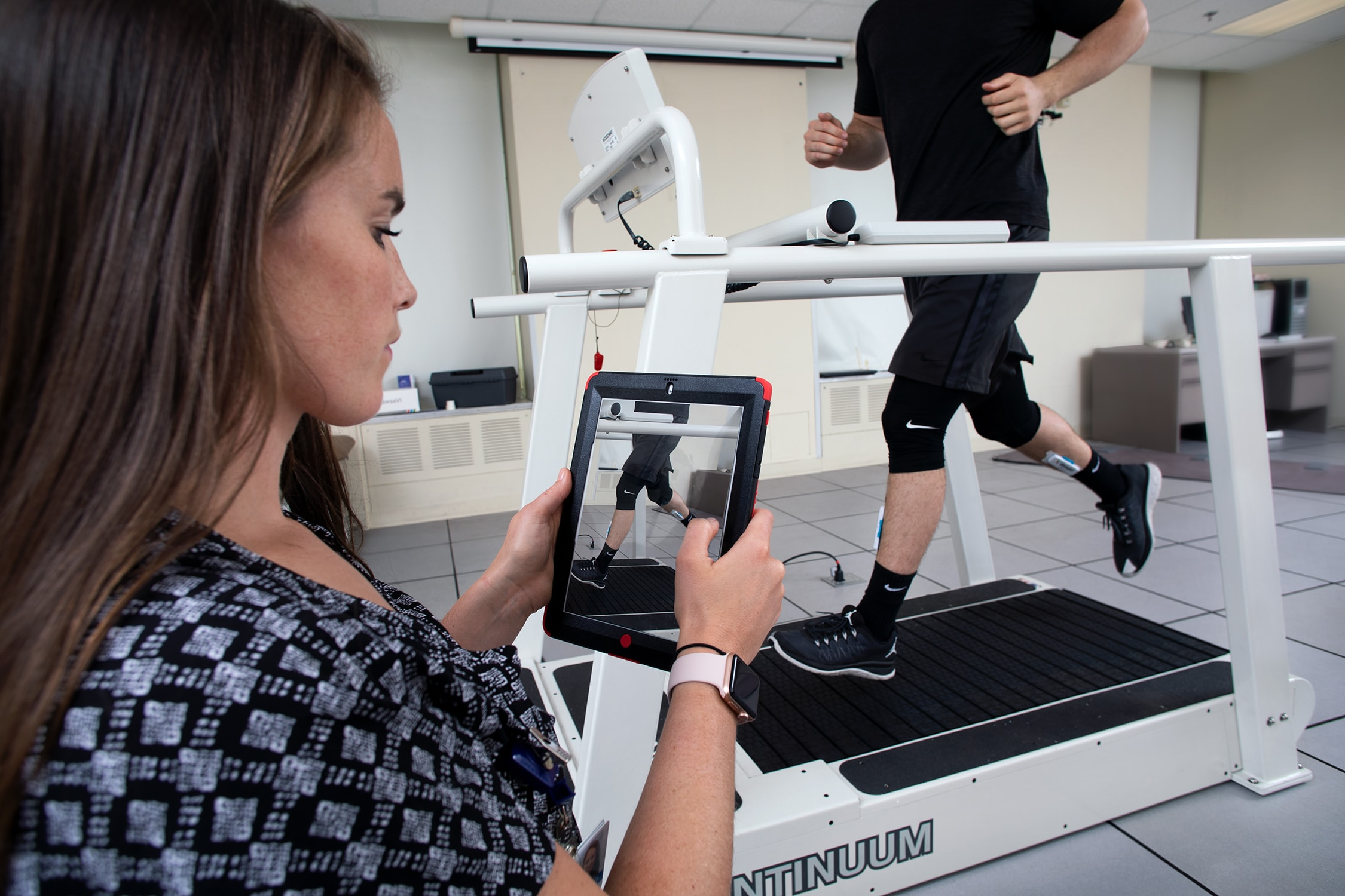 A man running on a treadmill while having a woman perform video gait analysis