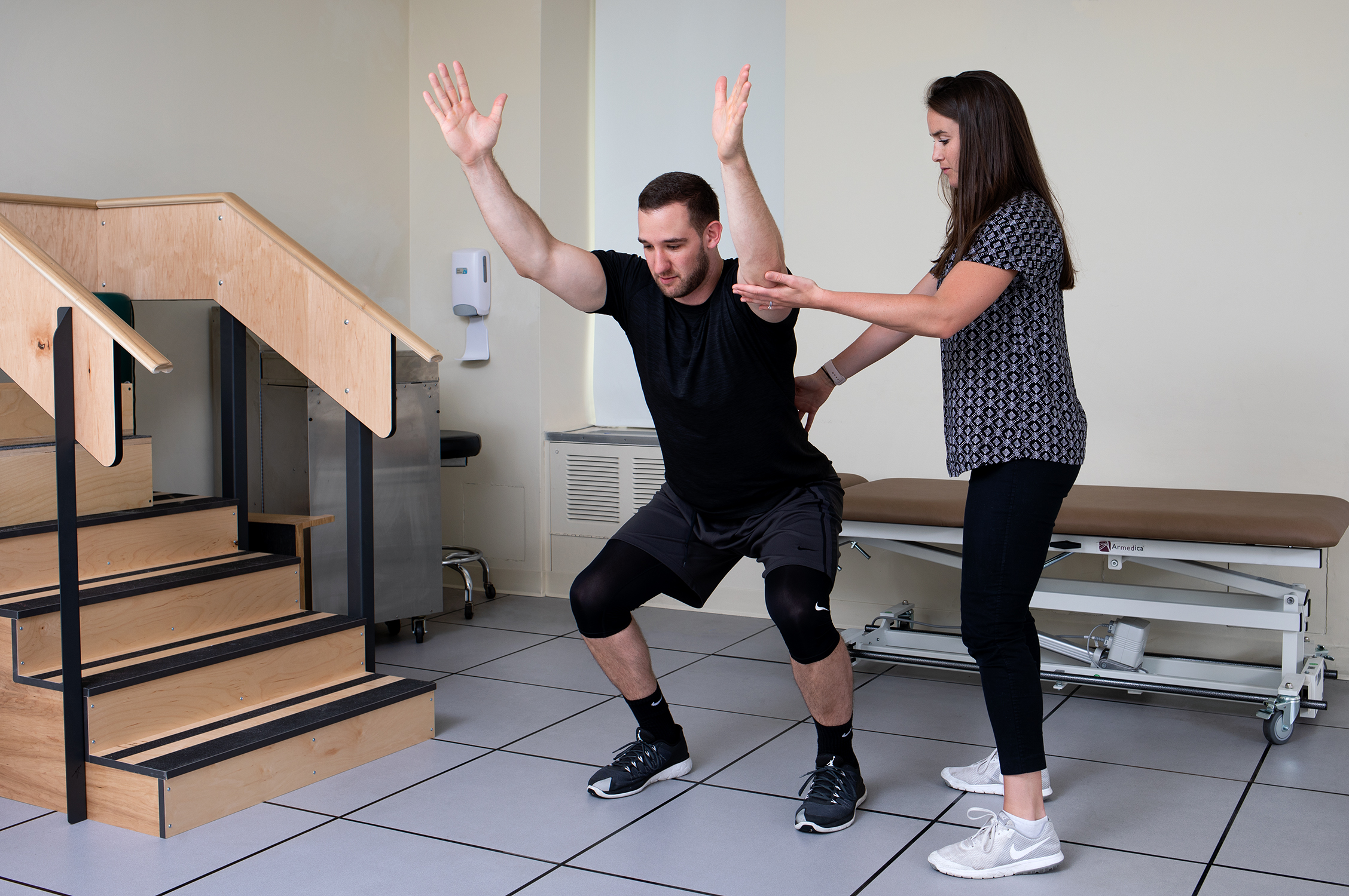 A physical therapist helping a man perform exercises