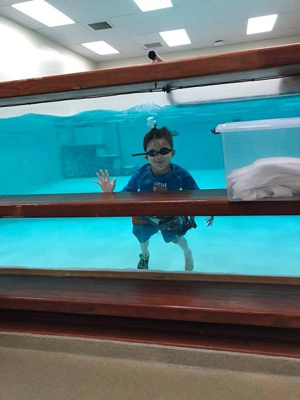 A young pool waving while underwater in a physical therapy pool