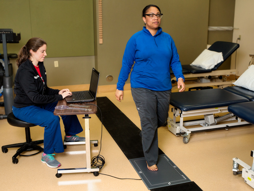 A woman being tested for an orthotic using foot pressure scanning technology